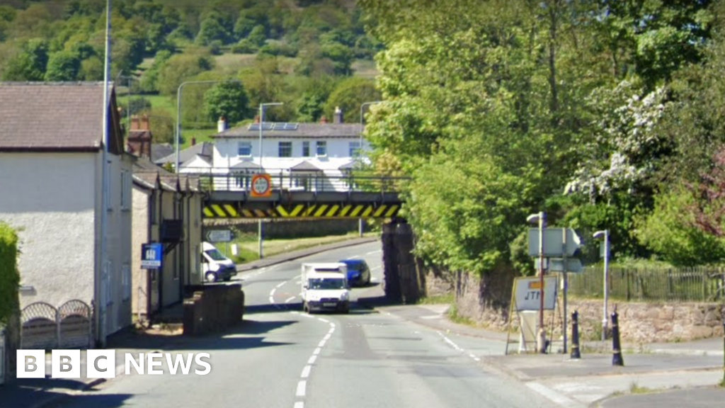 Cefn-y-bedd road closed with lorry stuck under bridge - BBC News